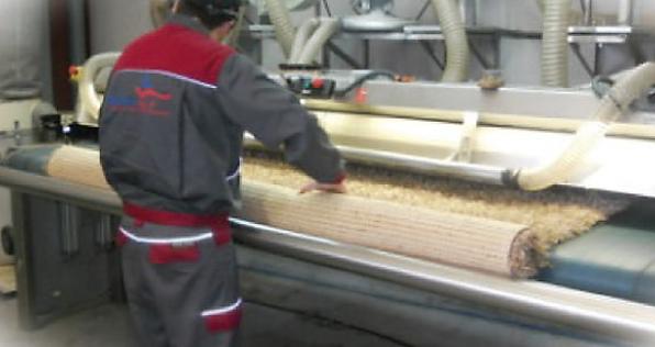 Fotografías de nuestros operarios en la nave de Mora Garay, en Gijón, durante el procesos de limpieza y desinfección de una alfombra persa.